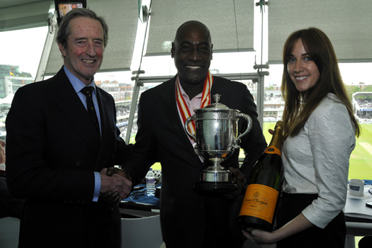 Brian Thornton presents Sir Vivian Richards with the Walter Lawrence Trophy and his medallions, while Lorraine Larmer, Senior PR & Communications Manager of Veuve Clicquot, is ready with the Champagne.